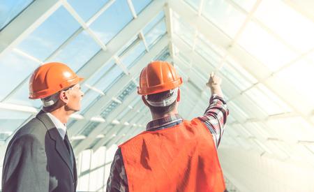 Gut aussehend Bauarbeiter und Geschäftsmann in Schutzhelmen untersuchen Bürozentrum photo