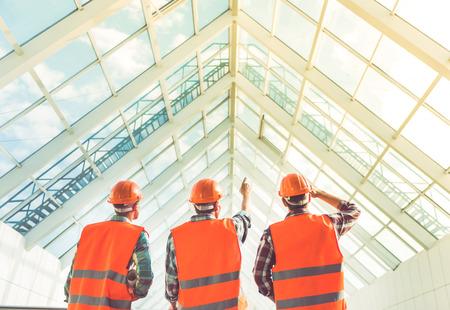 Achter mening van de werknemers in de bouw zich in het bureau centrum Stockfoto