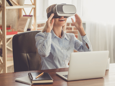 formal shirt: Beautiful business lady in formal shirt is using virtual reality headset and smiling while working with a laptop in the office