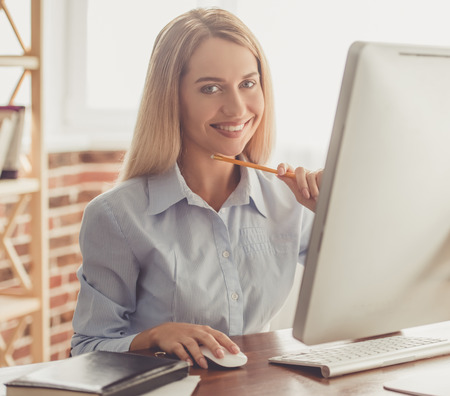 formal shirt: Beautiful business lady in formal shirt is using a computer and smiling while working in the office