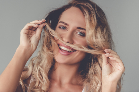 Portrait of beautiful blonde girl making moustache of her hair, looking at camera and smiling, on gray background