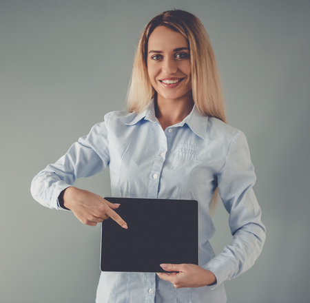 formal shirt: Beautiful business lady in formal shirt is showing a digital tablet, looking at camera and smiling, on gray background