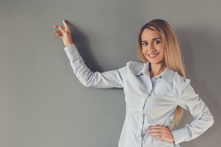 formal shirt: Beautiful business lady in formal shirt is pointing, looking at camera and smiling, on gray background