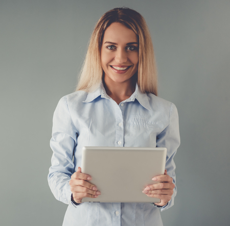 formal shirt: Beautiful business lady in formal shirt is using a digital tablet, looking at camera and smiling, on gray background
