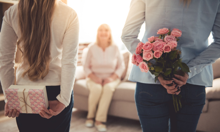 Teenage girl and her mom are hiding flowers and a gift box for their beautiful granny behind backs while grandma is sitting on couch at home Stock Photo