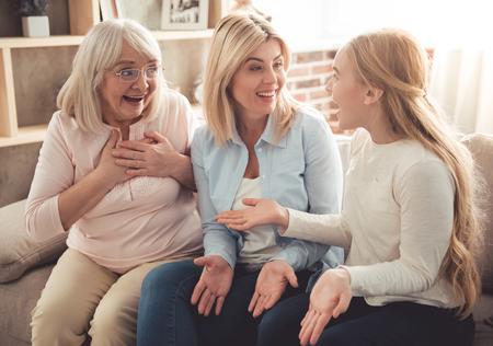 Tres generaciones de mujeres. Hermosa abuela, madre e hija abrazan, hablan y sonríen mientras está sentado en el sofá en casa Foto de archivo