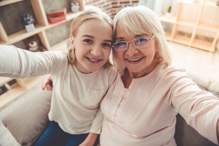 Hermosa abuela y su nieta están haciendo selfie, mirando a cámara y sonriendo mientras está sentado en el sofá en casa Foto de archivo