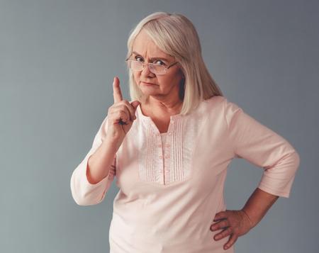 Belle femme mature à lunettes avertit et regarde la caméra, sur fond gris Banque d'images - 70224532