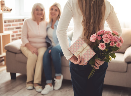 Cute teenage girl is hiding flowers and a gift box for her beautiful granny and mother behind her back while those are sitting on couch at home