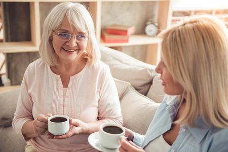 Hermosa madre madura y su hija adulta están bebiendo café, hablando y sonriendo mientras está sentado en el sofá en casa
