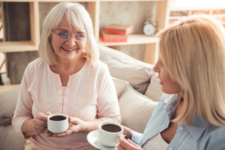 Schöne reife Mutter und ihre erwachsene Tochter trinken Kaffee, reden und lächelnd, während auf der Couch zu Hause sitzen