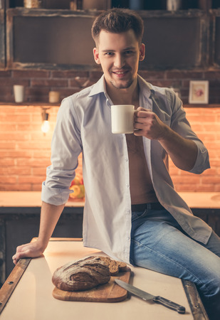 Handsome guy is drinking coffee, looking at camera and smiling while cooking in the kitchen