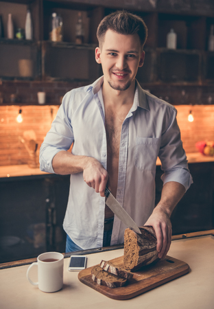 unbutton: Handsome guy is cutting bread, looking at camera and smiling while cooking in the kitchen Stock Photo