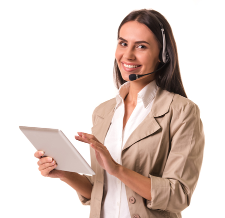 hear business call: Beautiful business lady in beige suit and headset is using a digital tablet, looking at camera and smiling, isolated on white