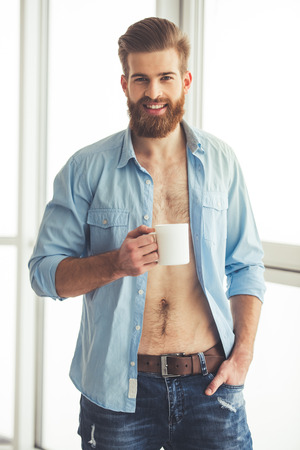 Handsome bearded man in unbuttoned shirt is holding a cup, looking at camera and smiling while standing near the window at home