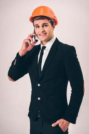 protective suit: Handsome young businessman in suit and protective helmet is talking on the mobile phone and smiling, on gray background