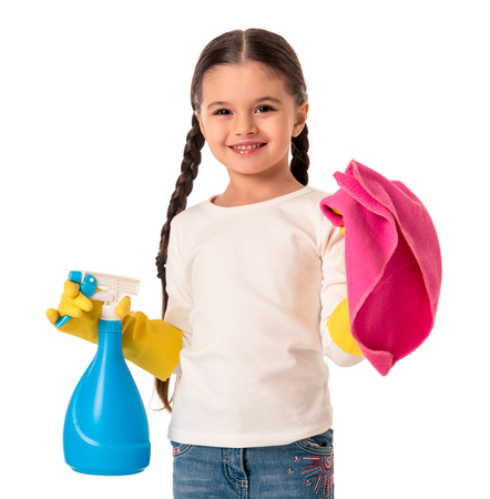 Cute little girl in protective gloves is holding a detergent and a duster, looking at camera and smiling, isolated on white