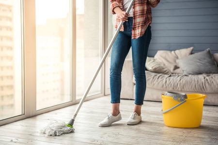 청소를 사용 하여 집에서 바닥을 청소하는 아름 다운 젊은 여자의 자른 된 이미지