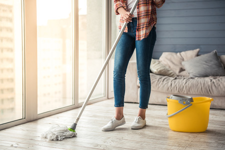 Cropped image of beautiful young woman cleaning floor at home using a mop