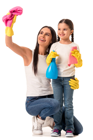 Beautiful young woman and her cute daughter in protective gloves are holding detergent and  duster, looking at camera and smiling, isolated on white Stock Photo