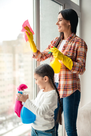 Beautiful young woman and her little daughter are smiling while cleaning window at home using detergent and rags