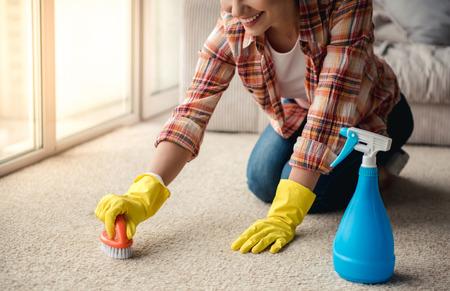 Hermosa mujer joven en guantes de protección es sonriente, con un detergente y un cepillo, mientras que la limpieza de la alfombra en casa