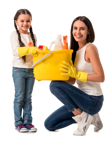 Beautiful young woman and her cute daughter in protective gloves are holding detergents and  duster, looking at camera and smiling, isolated on white