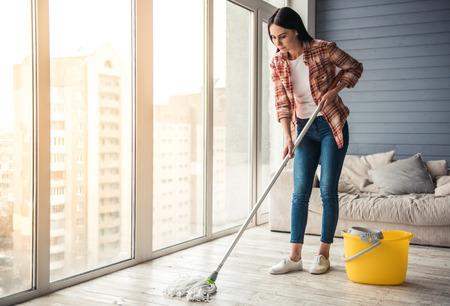 아름 다운 젊은 여자는 집에서 청소를 사용 하여 바닥을 청소하는 동안 웃