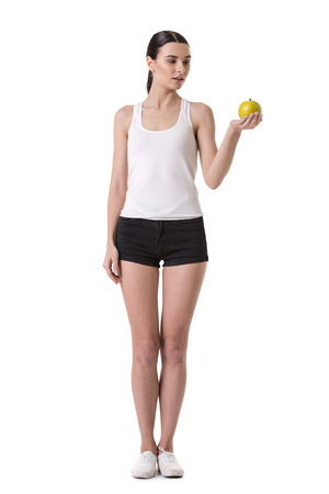 obsessed: Healthy nutrition. Full length image of girl holding an apple and looking at it, isolated on white