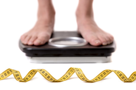 Cropped image of women feet standing on weigh scales, isolated on white. A tape measure in the foreground Stock Photo