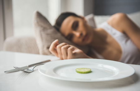 식욕 부진으로 고통. 포 그라운드에서 접시에 오이의 조각, 우울 소녀 배경에 누워