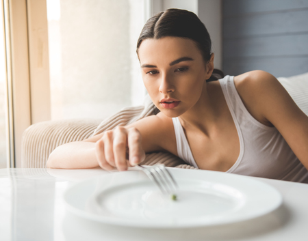 拒食症で苦しんでいます。女の子がフォークにエンドウ豆を入れしよう 写真素材