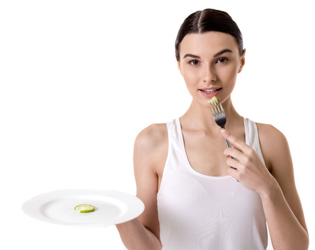 Eating disorder. Girl is holding a plate with a slice of cucumber on it and looking at camera, isolated on white Stock Photo