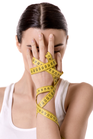 Portrait of girl covering her face, isolated on white. Hand wrapped in a tape measure