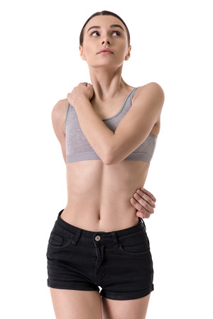 Suffering from anorexia. Girl is throwing her arm around her waist, isolated on white