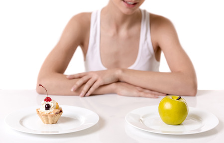 Eating disorder. Girl is sitting at the table and choosing between a cake and an apple, isolated on white Stock Photo