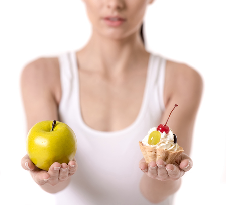 Healthy nutrition. Cropped image of girl holding a cake and an apple, isolated on white