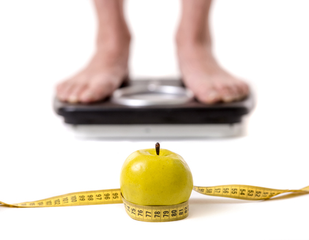 Cropped image of women feet standing on weigh scales, isolated on white. A tape measure and an apple in the foreground Stock Photo