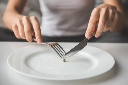 Lijden van anorexia. Bijgesneden afbeelding van meisje probeert een erwtje op de vork te zetten