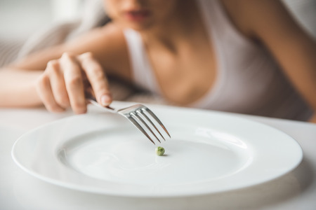 Suffering from anorexia. Cropped image of girl trying to put a pea on the fork