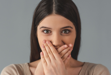 adult oops: Attractive young woman in casual clothes is covering her mouth and looking at camera, on gray background Stock Photo