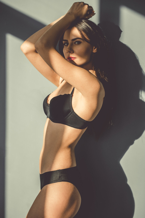 glamour nude: Beautiful young woman in black lingerie is looking sensually at camera while standing near the wall with sunlight