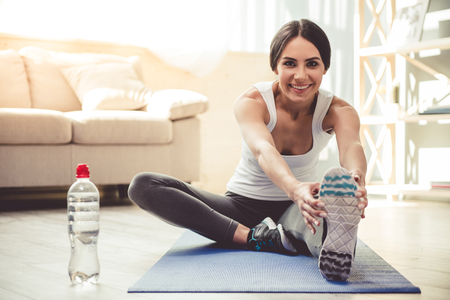 De mooie jonge vrouw in sportkleding glimlacht terwijl thuis het uitrekken op yogamat Stockfoto