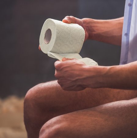 Cropped image of handsome Afro American man holding a toilet paper while sitting on toilet