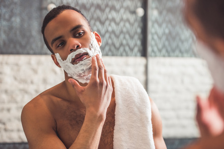 Handsome Afro American man is applying shaving foam while looking into the mirror in bathroom