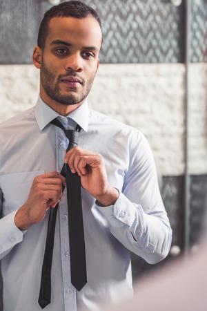 클래식 셔츠에 잘 생긴 아프리카 계 미국인 사업가 화장실에서 거울에 찾고있는 동안 넥타이 매듭입니다.