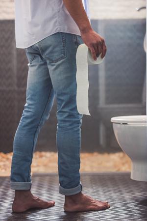 Imagen recortada de apuesto hombre afroamericano en pantalones vaqueros sosteniendo un papel higiénico mientras está de pie cerca del inodoro