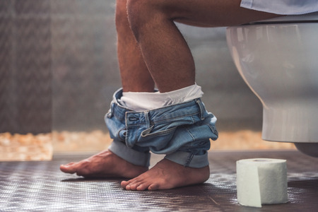 Cropped image of handsome Afro American man sitting on toilet. His jeans is hanging on his legs