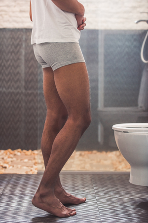 Cropped image of handsome Afro American man in boxer shorts keeping hands on his belly while standing near the toilet
