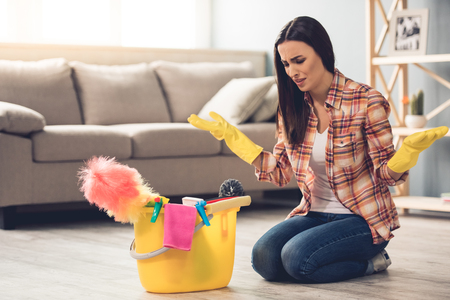 Beautiful tired young woman in protective gloves is sitting confused near the bucket with things for cleaning while cleaning her house